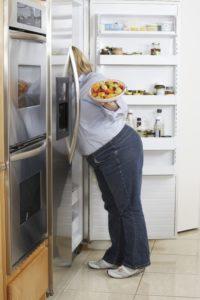 Woman looking in the refridgerator.