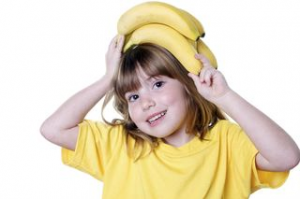 little girl with bananas on her head