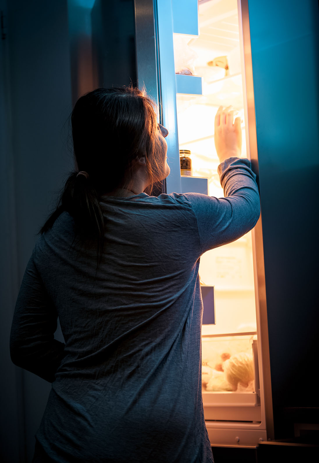 Portrait of young woman opening refrigerator at night