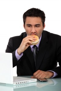 businessman-eating-hamburger-at-desk