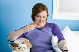 Overweight woman watching tv eating pastries