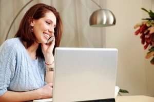 Cheerful woman talking on the phone at her workplace at home