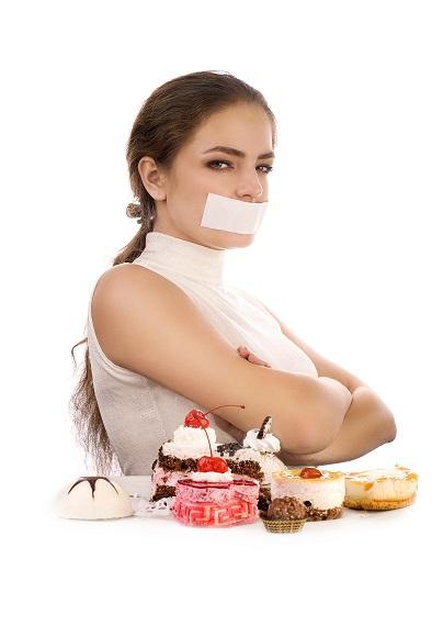 Young beautiful woman refusing pastries
