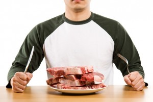 man with pile of steaks