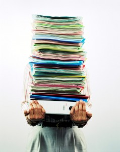 stressed man holding stack of files