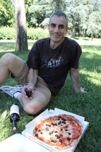 Owen eating pizza in a park in Bologna Italy.