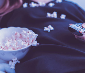 Woman holding TV remote eating popcorn.