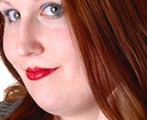 A very pretty young woman in a portrait shot, wearing a gray dress and red brunette hair, looking into the camera for white background.